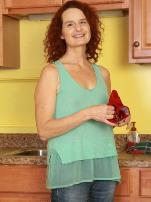 Redheaded 49 year older housewife Gloria M getting naked inwards the kitchen