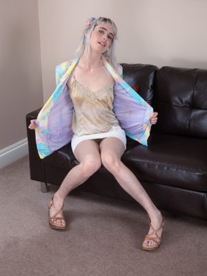 Esme strips naked on her brown leather sofa
