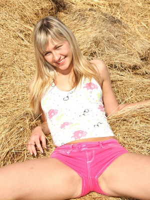 Cute teenage girl masturbating outside in a pile of hay
