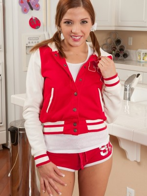 Redhead teenage Evilyn Fierce takes off off her school letter jacket.