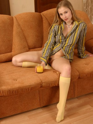 Golden-haired hottie lazily unclothes on the ottoman