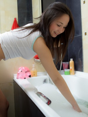 Cute brunette hair fucking her pussy with a big pinkish dildo in the bath