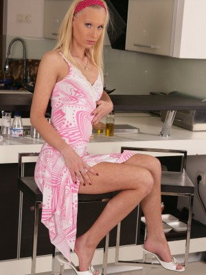 Sweet blond lazily undresses on the table