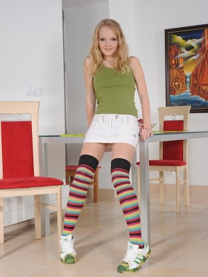 Golden-haired coed Goldie fingers beaver while undressed in knee high socks.