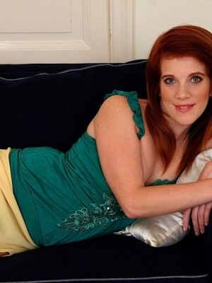 Provocative redhead Roxy Rush stretches pussy lips.